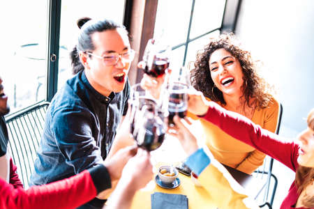 Young multiracial friends drinking and toasting red wine at dinner party - Happy drunk people having fun together at restaurant winery bar - Dinning life style concept on warm bright backlight filter
