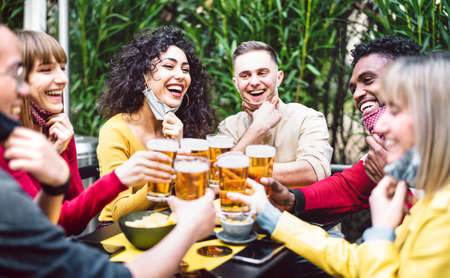 Young people toasting beer wearing open face mask Фото со стока