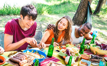 Happy people having fun together at barbecue picnic party - Young multiracial friends at pic nic social gathering - Youth life style concept with guys and girls eating at barbeque - Warm bright filter Фото со стока