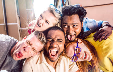 Multiracial millenial people taking selfie sticking out tongue with happy faces - Funny life style concept against racism with international young friends having fun together - Warm bright filter