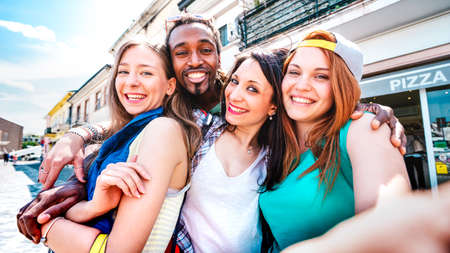 Multicultural tourists group taking selfie at old town tour - Happy millenial life style concept with young people having fun around city after lockdown reopen - Bright vivid filter with focus on face