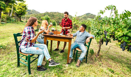 Happy people having fun drinking red wine at vineyard - Young friends enjoying harvest time together at country side farm house - Youth life style concept on warm filter