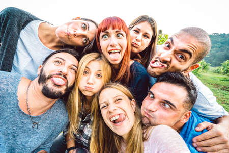 Best friends taking funny selfie at picnic excursion sticking out tongue - Youth life style concept with young people having fun together outdoors - Warm bright filter with focus on central faces