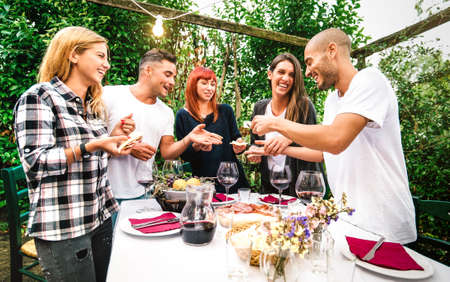 Young people having fun eating local food and drinking red wine at country side garden fest - Friendship and life style concept with happy friends together at farmhouse patio party - Warm vivid filter Фото со стока