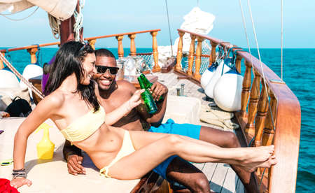 Young couple in love on sailing boat cheering with beer bottles - Happy girlfriend and boyfriend making party at cruise travel on luxury sailboat - Bright vivid filter with focus on faces