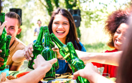 Happy millenial friend having fun at barbecue garden party - Life style and friendship concept with young people toasting bottled beer at summer hangout - Warm bright filter with focus on bottles