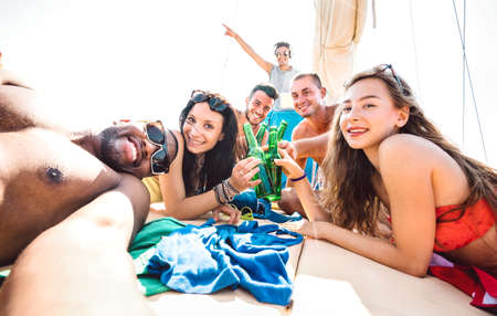 Friends group of guys and girls taking selfie at sailing boat - Luxury life style concept with young multiracial people having fun together at summer beach vacation - Bright vivid sunshine filter Фото со стока