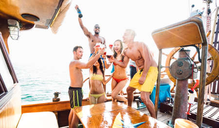 Multiracial millennial friends having fun dancing at sail boat party - Luxury life style concept with young multi ethnic people on sailboat excursion - Happy travel mood on bright backlight filter