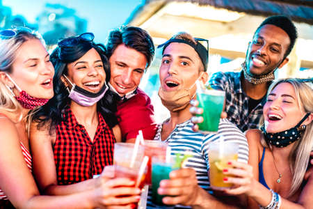 Happy multicultural people toasting at night bar with open face masks - New normal life style concept with milenial friends having fun together - Shallow depth of field with focus on middle guy