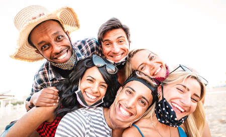 Multiracial friends taking selfie smiling over open face masks - New normal life style friendship concept with young people having fun together after lockdown reopening - Warm bright backlight filter