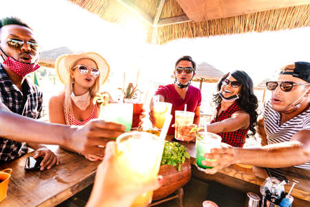 Young multiracial people toasting at beach cocktail bar with open face mask - New normal life style summer concept with happy friends having fun together cheering drinks - Warm backlight filter 스톡 콘텐츠