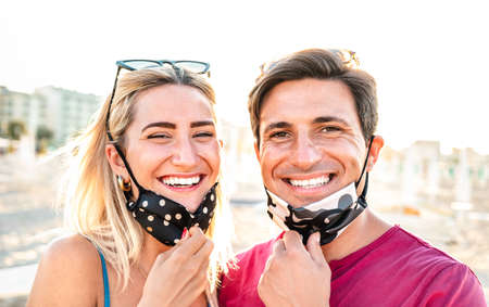 Young couple in love smiling with open face mask - New normal life style and relationship concept with happy lovers on positive mood at beach after lockdown reopening - Bright warm backlight filter 스톡 콘텐츠