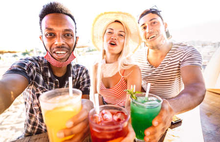 Multiracial people trio taking selfie with open face masks at beach bar - New normal life style concept with drunk friends having fun together at summer resort vacation - Bright warm backlight filter 스톡 콘텐츠