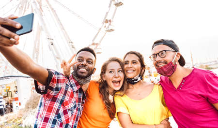Multicultural happy travelers taking selfie wearing open face masks - New normal travel life style concept with young friends having fun together at public ferris wheel - Bright warm filter