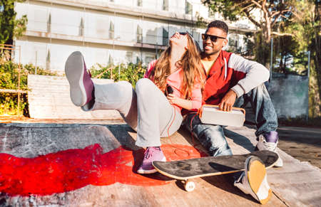 Multiracial couple having fun together at skate park with music boombox - Urban life style concept with genuine people outdoors at love story beginnings - Sunny day with warm contrasted filtered tones