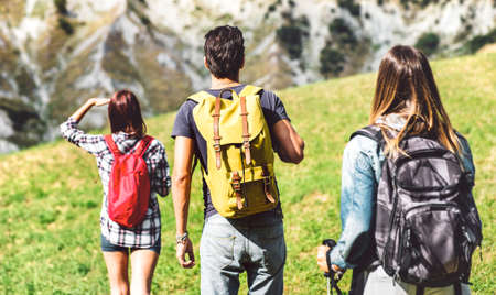 Friends group trekking on italian alps at afternoon - Hikers walking on mountain place - Wanderlust travel concept with young people at excursion in wild nature - Focus on central yellow backpack