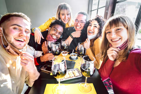 Friends taking selfie at winery with open face mask - People having fun together drinking red wine glasses at restaurant reopening - Selective focus on middle guys and girls with warm contrast filter