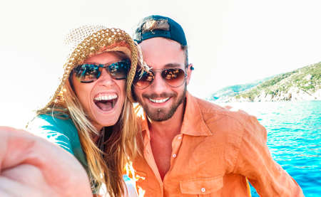 Young happy couple in love taking selfie at sailboat excursion with water camera - Boat trip life style in exotic scenarios - Youth lifestyle and travel concept around the world - Warm bright filter 스톡 콘텐츠