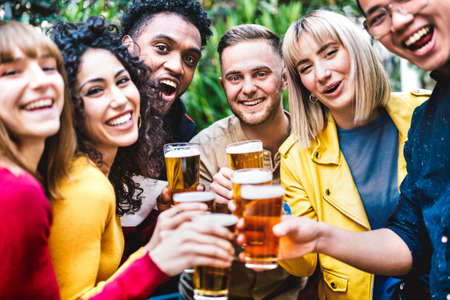Happy friends toasting beer at brewery bar dehor - Friendship life style concept with young millennial people enjoying time together at open air pub - Warm vivid filter with focus on central guy Foto de archivo