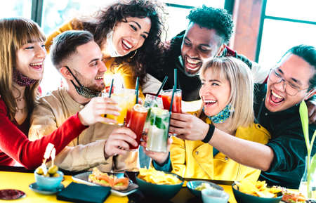 Happy multiracial friends toasting drinks with open face masks - New normal life style concept with youngfriends having fun together after lockdown reopening - Vivid filter with focus on left guy 스톡 콘텐츠