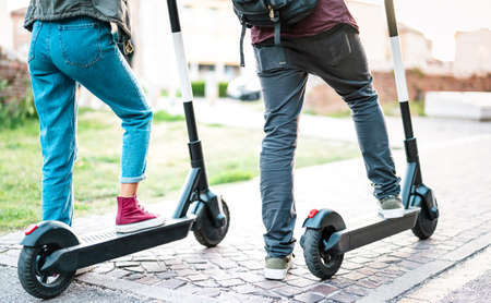 Close up of city commuters using electric scooter at urban park - Millenial students riding new modern ecological mean of transport - Green eco energy concept with zero emission - Bright retro filter