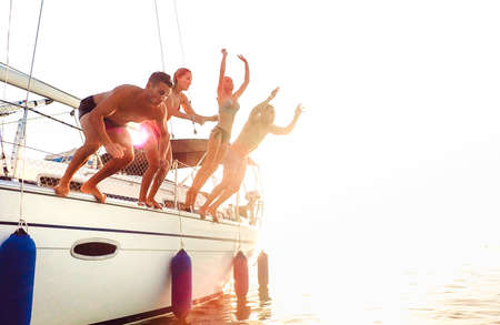 Side view of young crazy friends jumping from sailboat on sea ocean trip - Men and women having summer fun together at sail boat party day - Luxury excursion concept on warm backlight filter 스톡 콘텐츠