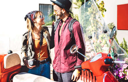 Young tourist couple having fun together at scooter moped ride - Hipster guy having fun outdoors with beautiful girlfriend - Happy travel mood and life style concept on spring day - Warm bright filter
