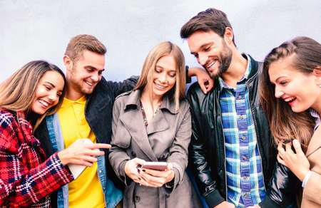 Milenial friends on fun moment using mobile smart phone - Young people always connected at social media devices - Technology concept with modern teenagers sharing content online - Bright vivid filter