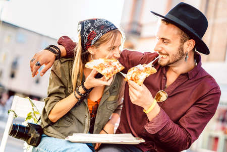Young hipster couple eating pizza at bar restaurant outdoors - Happy relationship concept with millenial boyfriend and girlfriend having fun moments together - Bright vivid filter with focus on faces