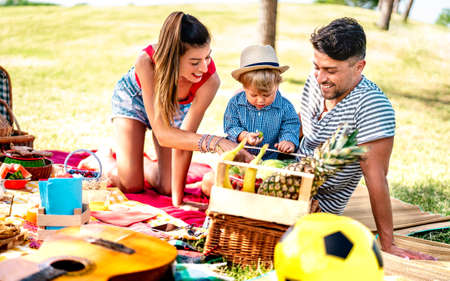 Happy family having fun together at picnic party - Joy and love life style concept with mother and father playing with child at park - Warm bright filter with focus on faces 스톡 콘텐츠