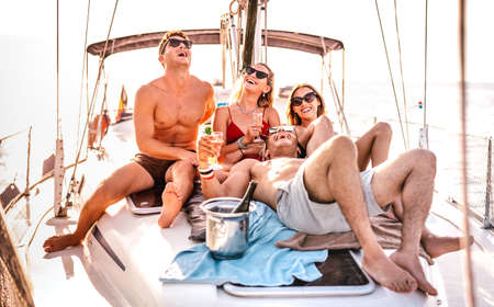 Happy young friends having fun at sailboat party - Wanderlust travel concept with millenial people on sailing trip - Luxury lifestyle on exclusive summer mood - Warm sunshine halo filter