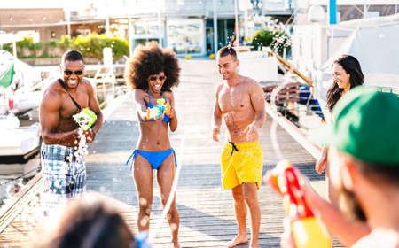 Crazy happy friends having genuine fun with waterfight battle at summer location - Alternative vacation concept with young guys and girls using water gun at beach docks