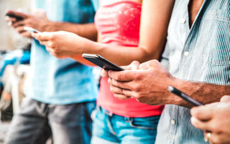 Cropped view on milenial hands using mobile smartphones - People addicted by smart phones - Technology concept with always connected teenagers 스톡 콘텐츠