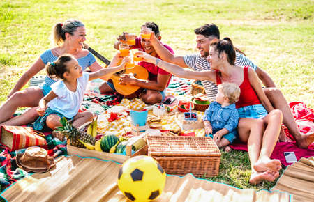 Multiracial families having fun together with kids at pic nic barbecue party - Joy and love life style concept with mixed race people toasting juices with children at park Stockfoto