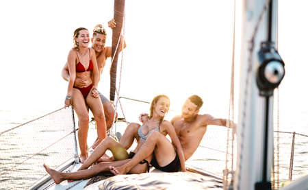 Young couple friends chilling on sailboat at sea ocean trip - Guys and girls having summer fun together at sail boat party day - Luxury concept on warm bright filter
