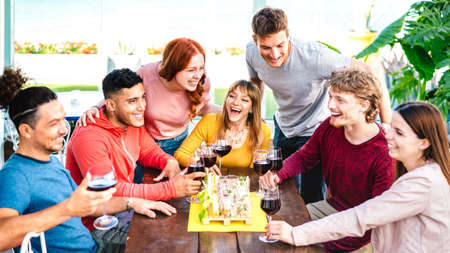 Happy friends having fun together drinking wine at rooftop on private house party - Young people eating finger food at restaurant - Dinning life style concept on vivid filter 스톡 콘텐츠