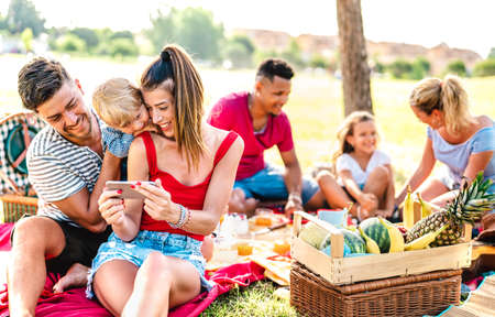 Happy multiethnic families playing with phone at pic nic garden party - Joy and love life style concept with mixed race people having fun together at picnic barbecue before sunset 스톡 콘텐츠