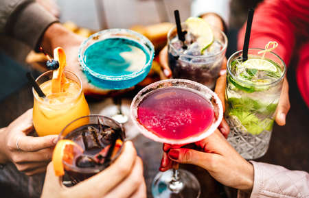 People hands toasting multicolored fancy drinks - Young friends having fun together drinking cocktails at happy hour - Social gathering party time concept on warm vivid filter 스톡 콘텐츠