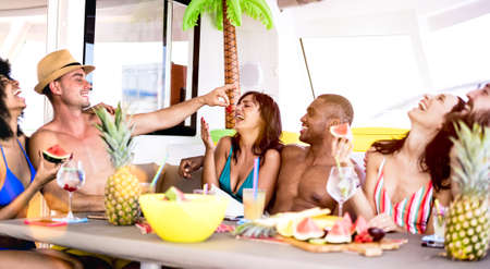 Happy friends drinking tropical cocktails at boat party - Young millennial people having fun on luxury vacation - Travel life style concept with millenials playing with drinks with fruit