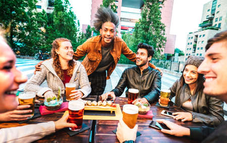 Young people drinking beer at brewery bar dehor - Friendship lifestyle concept with multicultural friends spending happy hour time together at open air pub garden - Warm bright filter