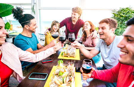 Happy millenial people having fun together drinking wine at terrace  on private house party - Young friends eating finger food at restaurant reopening 스톡 콘텐츠