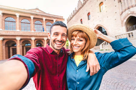 Young boyfriend and girlfriend in love having fun taking selfie at old town tour - Wanderlust life style travel concept with tourist couple on city sightseeing vacation