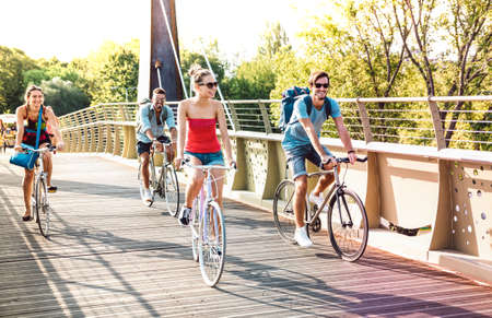 Happy milenial friends having fun riding bike at city park bridge - Life style concept with young hipster students biking together on bicycle lane