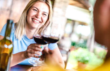 Tilted crop of happy couple toasting red wine at countryside restaurant - Food and beverage life style concept with boyfriend and girlfriend on having fun drinking together 스톡 콘텐츠