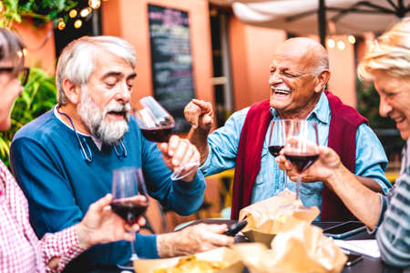 Happy retired friends having fun drinking red wine at pre dinner party - Senior people eating at restaurant together - Dinning life style concept on warm contrast filter