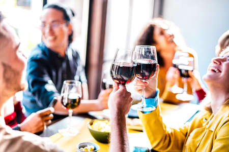 Young multiethnic people drinking and toasting red wine at lunch party - Happy drunk friends having fun together at restaurant winery bar