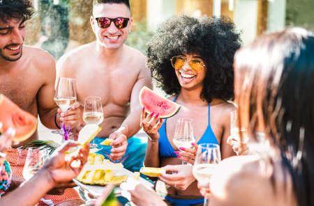 Happy friends group drinking white wine champagne at pool side party - Life style vacation concept with young guys and girls having fun together on summer day at luxury location
