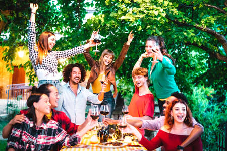 Friends having fun outdoor toasting red wine at garden party - Happy people eating and drinking together in farmhouse winery at night - Friendship concept on warm vivid filter