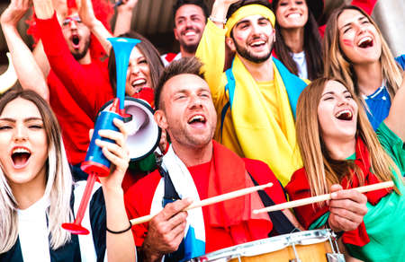 Football supporter fans cheering with drums watching soccer cup match at stadium bleachers - Young people group with multicolored t-shirt having excited fun on sport championship