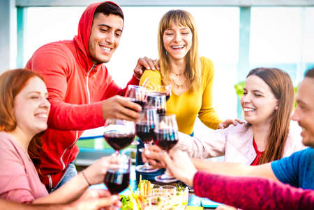 Young people toasting red wine at dinner party on multicolored clothes - Happy drunk friends having fun together at restaurant winery bar - Dinning life style concept